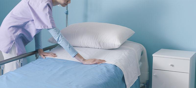 Zentratex, das sind Wäscheprofis für Kliniken. Hier: Eine Klinikmitarbeiterin, die ein bett vorbereitet.