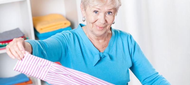 Zentratex, das sind Wäscheprofis für Seniorenheime. Hier: Eine ältere Dame legt Wäsche zusammen.
