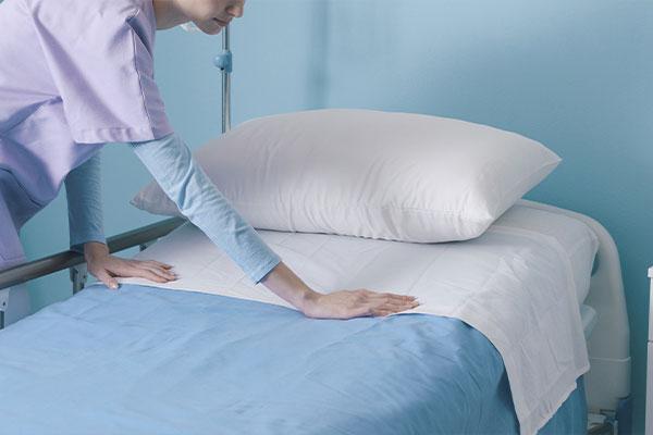 Kliniken & Reha - Bettwäsche und Frotteewäsche. Hier im Bild: Pflegekraft bezieht ein Bett frisch.