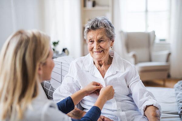Pflegerin hilft einer Bewohnerin beim Anziehen. Bewohnerwäsche wird bei Zentratex mit viel Fürsorge behandelt.