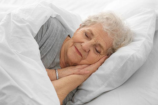 Senioren- & Pflegeheime - Bettwäsche und Frotteewäsche. Hier im Bild: eine Dame, die ihren Schlaf in frischer Bettwäsche genießt.